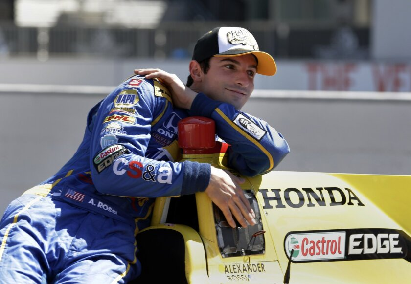 Indianapolis 500 champion Alexander Rossi relaxes as he poses during the traditional winners photo on the start/finish line at Indianapolis Motor Speedway in Indianapolis, Monday, May 30, 2016. Rossi won the 100th running of the Indianapolis 500 auto race on Sunday. (AP Photo/Michael Conroy)