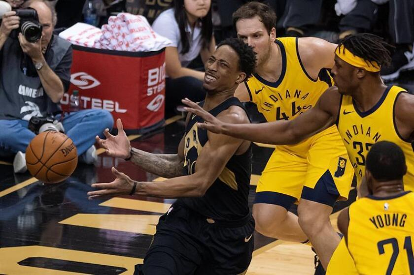 Toronto Raptors guard DeMar DeRozan (L) loses control of the ball under the basket after being blocked by Indiana Pacers forward Bojan Bogdanovic (R, back), forward Myles Turner (R) and forward Thaddeus Young in the first half of their NBA basketball game in Toronto, Canada. EFE