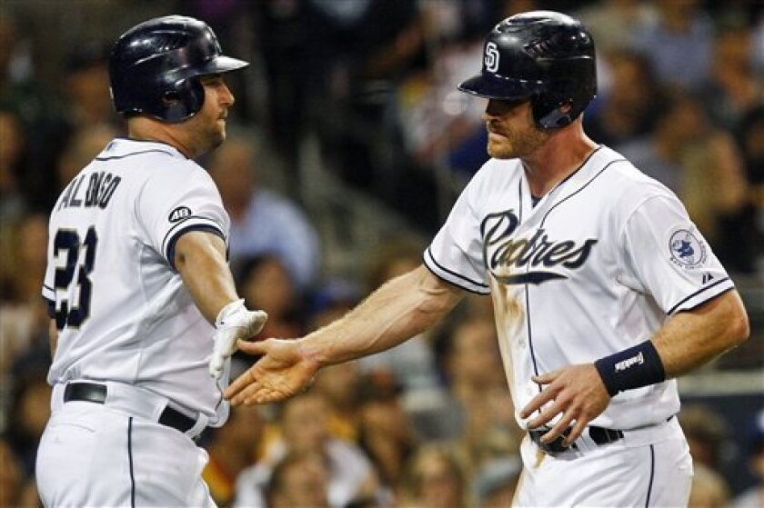 San Diego Padres' Logan Forsythe, right, is congratulated by Yonder Alonso after scoring against the Los Angeles Dodgers during the fourth inning of a baseball game, Tuesday, Sept. 25, 2012 in San Diego. Forsythe scored from third on a infield ground out by Yasmani Grandal. (AP Photo/Lenny Ignelzi)