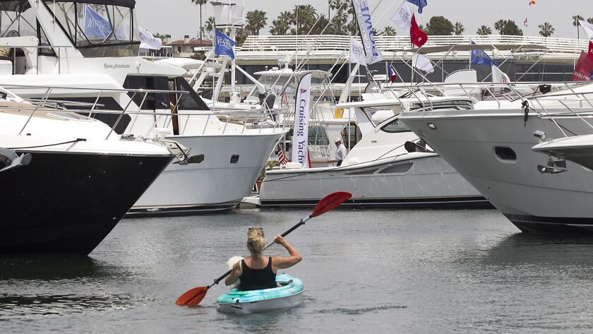 Rhonda Schneider with her dog Casey, uses her kayak for a closer look at several luxury boats docked