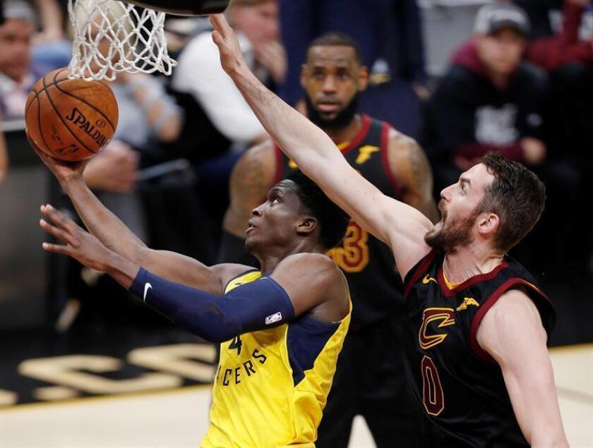 Victor Oladipo (i), de los Pacers de Indiana, fue registrado este domingo al atacar el aro que defienden Kevin Love (d) y LeBron James (c), de los Cavaliers de Cleveland, durante el primer partido de esta llave de postemporada de la NBA, en el Quicken Loans Arena de Cleveland (Ohio, EE.UU.). EFE