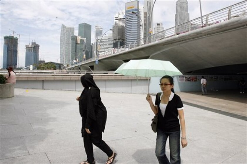 A muslim woman and a tourist walk in front of the Singapore Financial District on Wednesday, May 6, 2009 in Singapore. Most Asian economies face a sharp contraction this year and a weak recovery in 2010 as global demand for the region's exports struggles to rebound, the International Monetary Fund said Wednesday. Singapore's economy, which relies heavily on trade, finance and tourism, will likely shrink the most, contracting 10 percent this year and 0.1 percent next year. (AP Photo/Wong Maye-E)