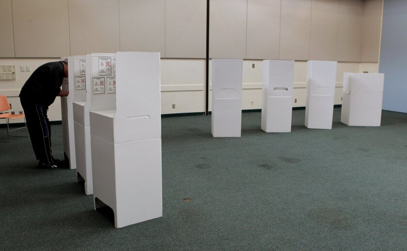 Voters make their choices in cardboard booths at the Oceanside Civic Center in 2014.