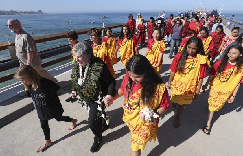 Mary Munk, widow of Walter Munk, holds hands with her granddaughter Alex Salazar, 12, left, and Sydney Fun, 13, while followed by young members of the Na Koa Kai Canoe Club as they walk back after watching a paddle-out Saturday.
