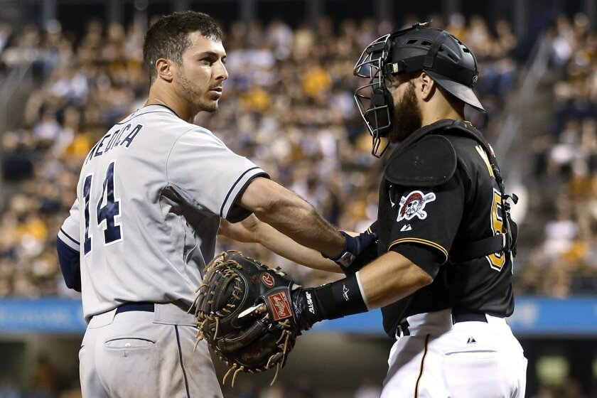 Pirates catcher Russell Martin, right, checks on Tommy Medica after the Padres hitter was hit in the head by a Jared Hughes pitch in Pittsburgh. The Pirates are hitting batters -- and having their batters hit -- more than any other MLB team for the second straight year.