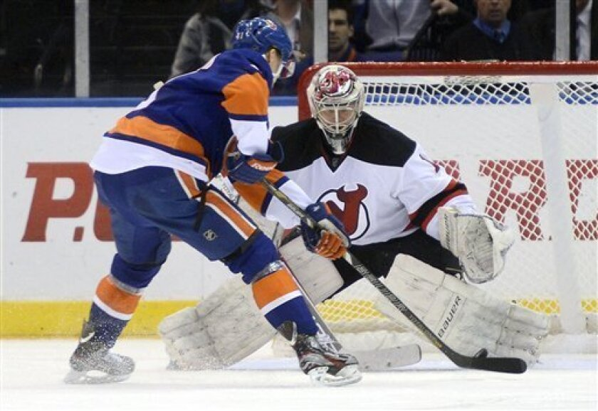 New York Islanders' David Ullstrom, left, fails to score on a penalty shot against New Jersey Devils goalie Johan Hedberg in the first period of an NHL hockey game in Uniondale, N.Y., Saturday, Feb. 16, 2013. (AP Photo/Henny Ray Abrams)