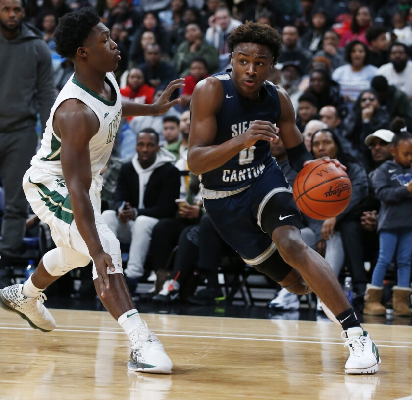 Sierra Canyon's Bronny James (0) drives against St. Vincent-St. Mary's Darrian Lewis during a game on Dec. 14, 2019, in Columbus, Ohio. James won't be under his father's watchful eye on Friday when playing against Mater Dei.