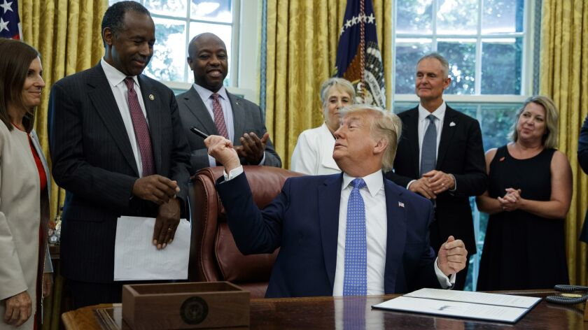 President Trump hands a pen to Secretary of Housing and Urban Development Ben Carson in the Oval Office on June 25, 2019.