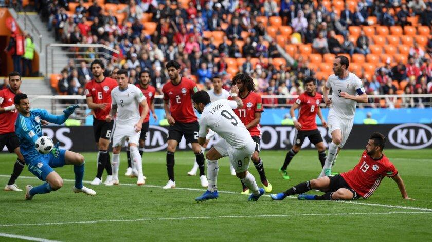 El delantero uruguayo Luis Suárez (c) estrella un balón en el portero egipcio.