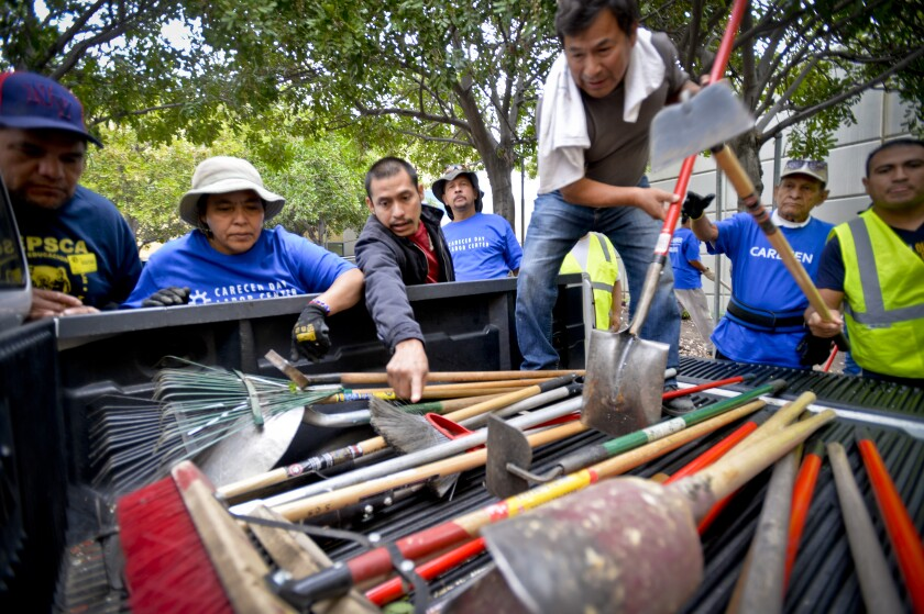 Day laborers from the CARACEN Day Labor Center and the IDEPSCA Labor Center pick out shovels and other tools