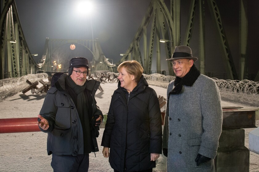 German Chancellor Angela Merkel talks on the set of the Glienicke bridge with director Steven Spielberg, left, and actor Tom Hanks.