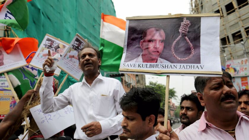 National Congress activists hold photographs of Indian national Kulbhushan Jadhav and placards again