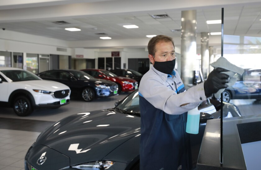 Rosendo Nevarez cleans glass at John Hine Mazda in Mission Valley. Nevarez makes rounds around the showroom cleaning surfaces. The dealer had one of its best sales weekends of the year over the Memorial Day weekend.