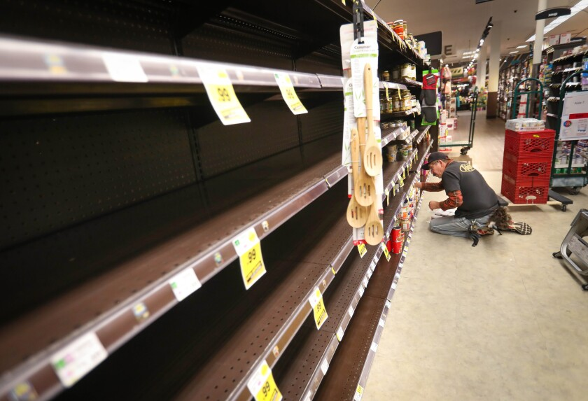 Jose Nunez, a grocery clerk at the Ralphs supermarket in the La Jolla Square shopping center, stocks empty shelves in the store, early in the morning, March 19, 2020 in San Diego, California.