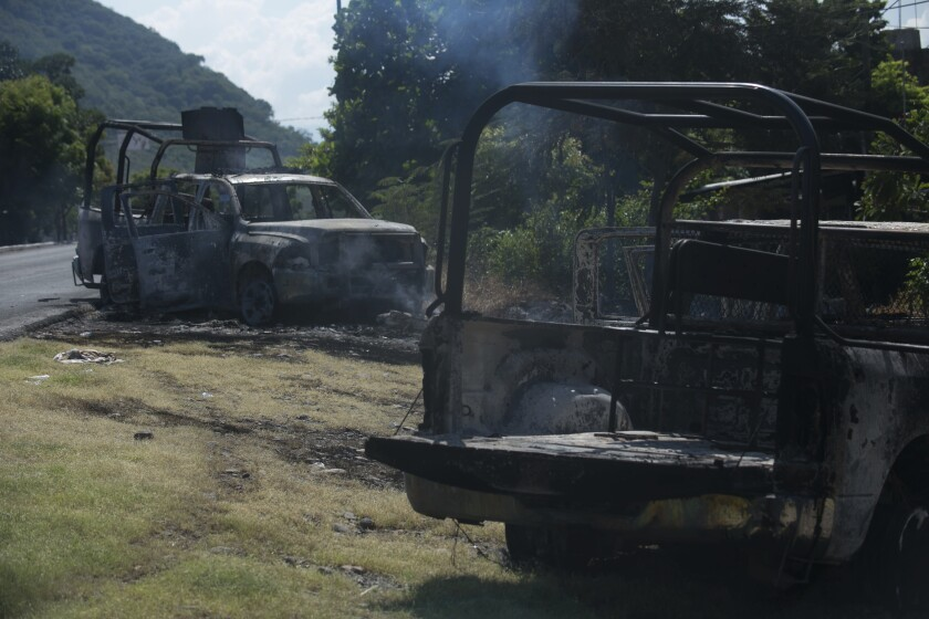 Charred trucks that belong to Michoacan state police stand on the roadside after they were burned during an attack in El Aguaje, Mexico, Monday, Oct. 14, 2019. At least 13 police officers were killed and three others injured Monday in the ambush. (AP Photo/Armando Solis)
