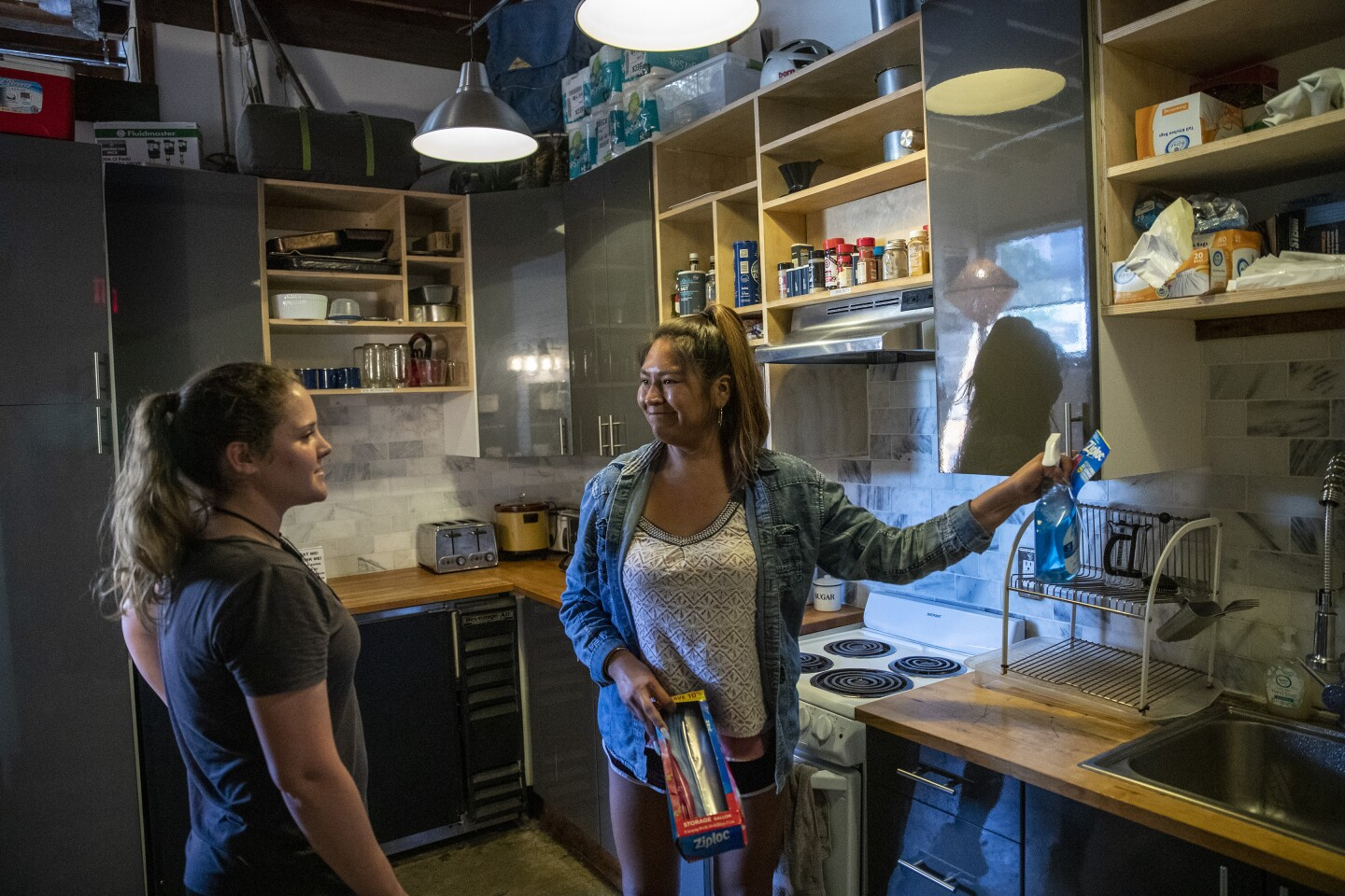 LOS ANGELES, CALIF. -- FRIDAY, OCTOBER 4, 2019: German tourist Lilly Geyer, 22, left, chats with front desk receptionist Blosson Manuel, right, in the common kitchen at PodShare Los Feliz in Los Angeles, Calif., on Oct. 4, 2019. (Brian van der Brug / Los Angeles Times)