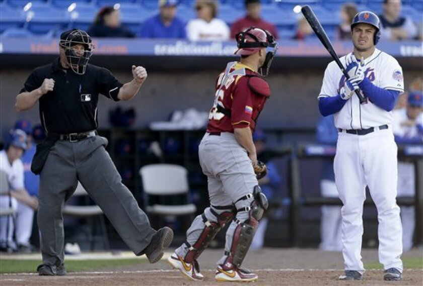Home plate umpire Chris Segal, left, gestures a called strike on New York Mets' Travis d'Arnaud, right, for the final out, next to Venezuela catcher Miguel Montero in anexhibition baseball game, Wednesday, March 6, 2013, in Port St. Lucie, Fla. Venezuela won 14-10. (AP Photo/Julio Cortez)