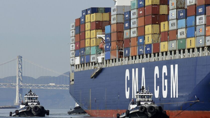 A container ship is guided by tugboats as it arrives at the Port of Oakland to be unloaded Thursday,