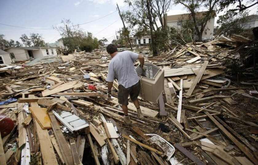 """Bill Higgins steps over debris as he looks for his neighbors' pets in Galveston, Texas. """"It's going to take weeks and months to get this place cleaned up,"""" City Manager Steve LeBlanc said."""