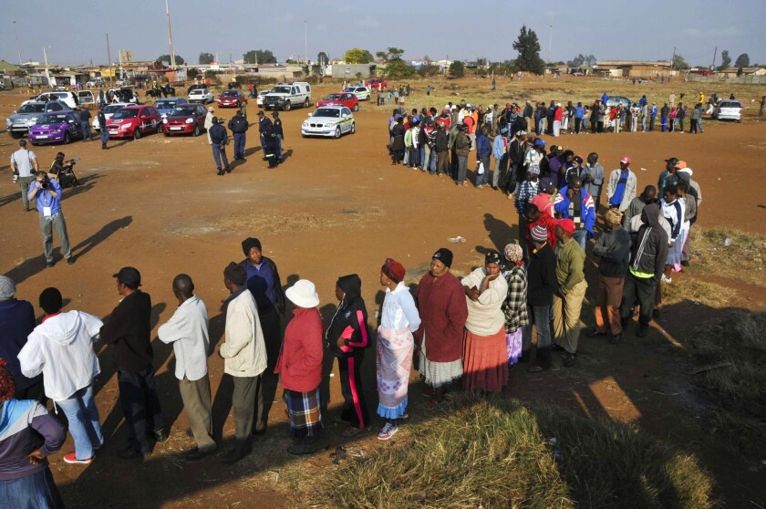 People line up at the entrance of a Bekkersdal, South Africa, polling station to cast ballots in a national election.