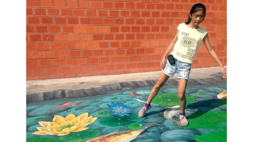 A child steps ona seascape painted on the ground of Haomei Village in Taiwan