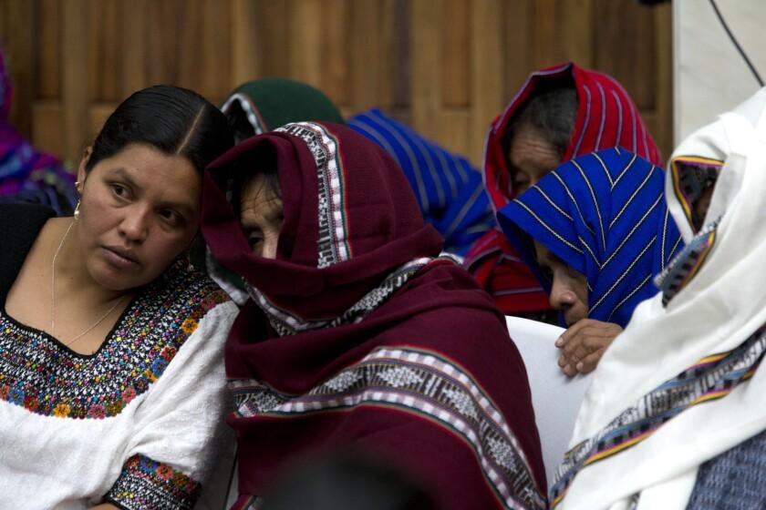 Víctimas de violencia sexual cubren sus rostros mientras escuchan a una intérprete, izquierda, en el primer día de un juicio contra un ex militar y un ex paramilitar en Guatemala. Ambos son juzgados por presunto asesinato, desaparición, violaciones sexuales y esclavitud laboral de al menos 15 mujeres durante el conflicto armado en Guatemala. (AP Photo/Moises Castillo)