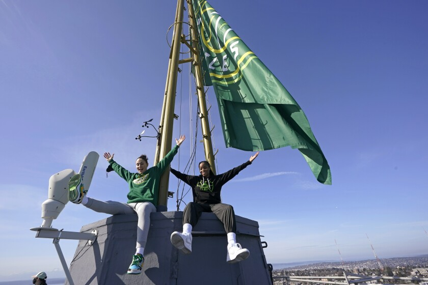 Seattle Storm guards Sue Bird, left, and Jordin Canada pose for photos Wednesday, March 3, 2021, on the roof of the Space Needle in Seattle after they raised a flag with the team's new logo on it. Bird re-signed with the Storm earlier in the week. (AP Photo/Ted S. Warren)