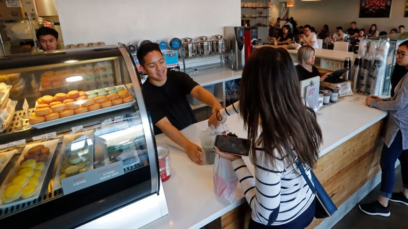 Shift leader Andy Ho fills a customers order at 7 Leaves Cafe in Garden Grove.