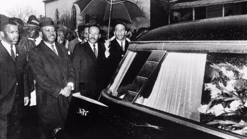 John Lewis, left, and the Rev. Martin Luther King Jr., center, in the funeral procession for Jimmie Lee Jackson, slain by an Alabama state trooper in Feb. 1965.