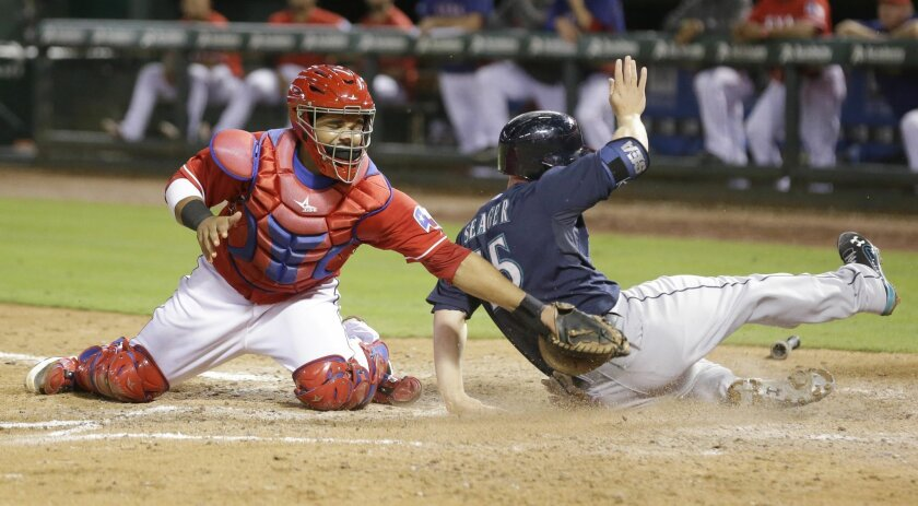 Seattle Mariners Kyle Seager (15) slides safely into home scoring against Texas Rangers catcher Tomas Telis (6) during the eighth inning of a baseball game early Sunday, Sept. 7, 2014, in Arlington, Texas. Seager scored on a single by Mariners Logan Morrison. (AP Photo/LM Otero)