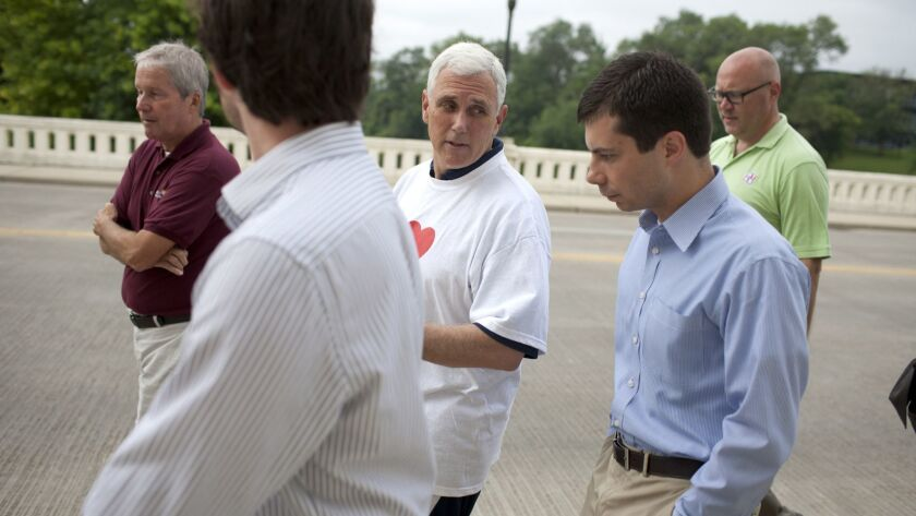 FILE - IN this July 3, 2013, file photo, then-Indiana Gov. Mike Pence, center, talks with South Bend