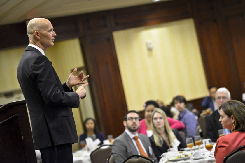 Florida Gov. Rick Scott speaks to an audience of business representatives in Woodland Hills in April 2015 during his last visit to try to lure California employers to his state. This week, he's back.