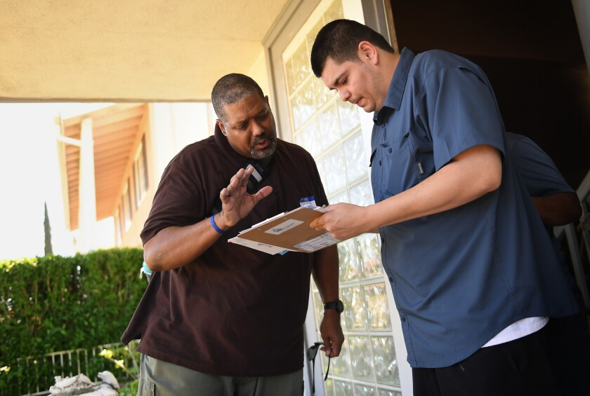 A volunteer from Los Angeles Derek Bryson, left, helps Erick Guillen, 25, sign up to vote by mail while knocking on doors in a Simi Valley neighborhood on Sunday, April 30, 2017 for the Simi Valley Democratic Club.