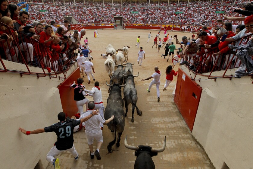 FILE- In this Sunday, July 14, 2019 file photo, revellers and fighting bulls arrive at the bullring during the running of the bulls at the San Fermin Festival, in Pamplona, northern Spain. The Spanish government is offering citizens who turn 18 years old next year 400 euros ($462) to spend on cultural activities. But the sum comes with strings attached: the recipients can't use it to buy tickets for bullfights. The decision was one of the politically controversial measures included in the 2022 national budget unveiled by the government Thursday, Oct. 7, 2021. (AP Photo/Alvaro Barrientos, File)