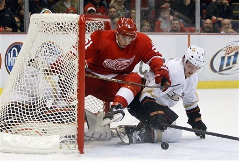 Michigan forward Valtteri Filppula, top, of Finland, and Anaheim Ducks defensemen Cam Fowler, right, collides into the net and Ducks goalie Jonas Hiller, of Switzerland, during the second period of an NHL hockey game, Saturday, Nov. 5, 2011, in Detroit. (AP Photo/Tony Ding)