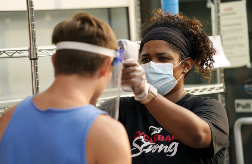 CycleBar employee Nia Freeman takes the temperature of a cyclist before a fitness class in Culver City.