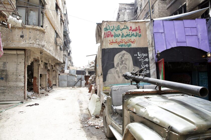 Graffiti is seen on a wall at the entrance to the Palestinian Yarmouk refugee camp south of Damascus on April 9.
