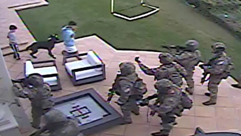 Heavily armed men stand on a patio near two children and a dog.