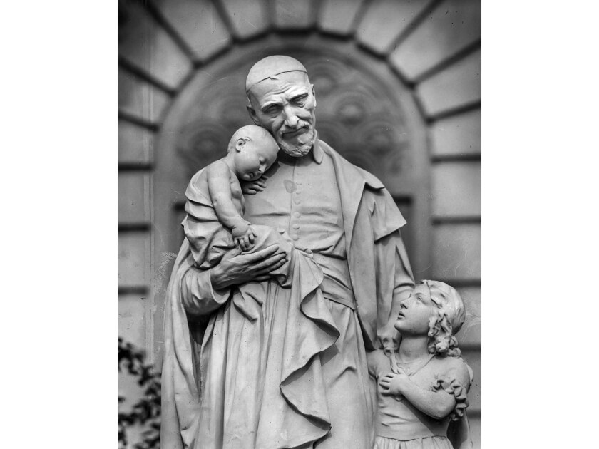 December 1955: Miniature statue of St. Vincent de Paul and the children that stands on the lawn in f
