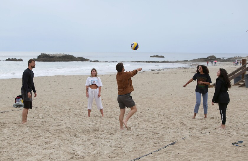 A group of friends plays volleyball without a net on Main Beach on Monday morning as Laguna Beach prepared to close city beaches and adjacent parks, including Main Beach, in an effort to prevent crowding that could help spread the coronavirus.