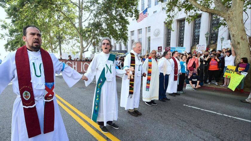 Clergy members hold hands as they block the road in front of the federal building in downtown Los Angeles to protest the Trump administration's immigration policies.