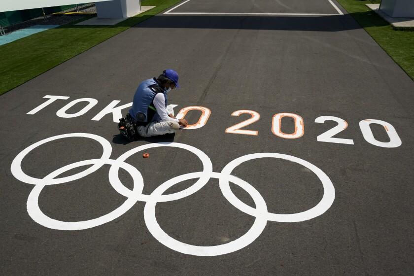 Un empleado pinta los anillos olímpicos en la meta de la pista del BMX previo a los Juegos Olímpicos