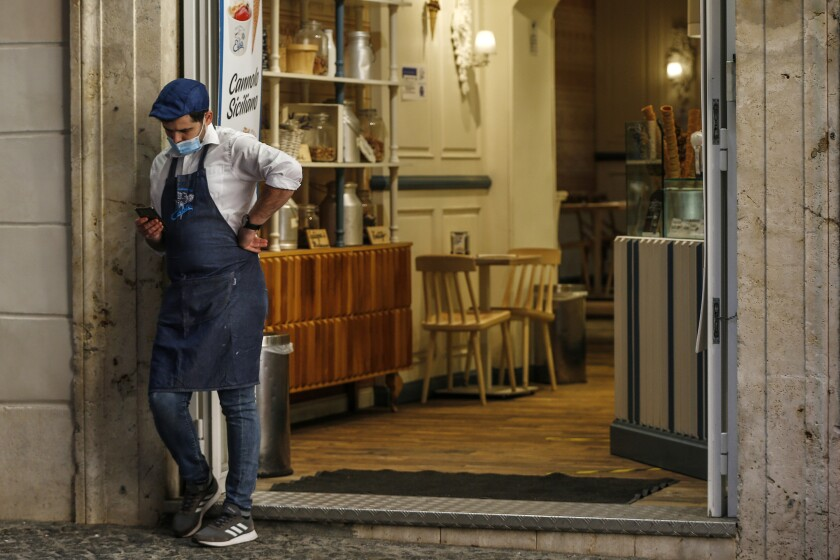 A waiter stands outside a cafe in downtown Rome on Sunday.