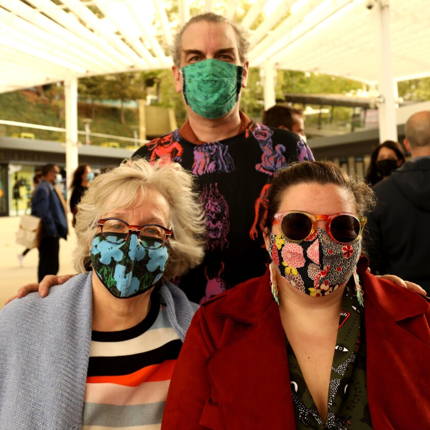 A man and two women in colorful face masks pose for a photo.