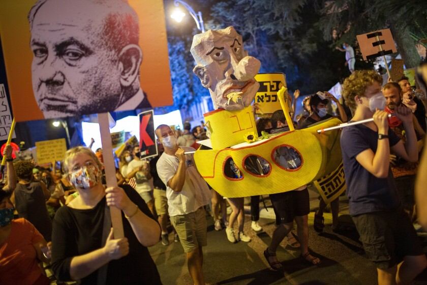 Demonstrators chant slogans and hold signs during a rally against Israel's Prime Minister Benjamin Netanyahu outside his residence in Jerusalem, Saturday, Aug 1, 2020. Protesters demanded that the embattled Israeli leader to resign as he faces a trial on corruption charges and grapples with a deepening coronavirus crisis. (AP Photo/Oded Balilty)