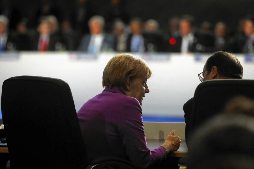 German Chancellor Angela Merkel speaks with French President Francois Hollande at a NATO meeting in Newport, Wales, on Sept. 5, 2014.