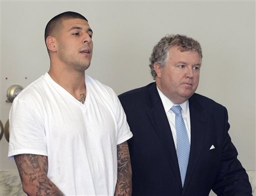 FILE - In this June 26, 2013, file photo, Aaron Hernandez, left, stands with his attorney, Michael Fee, right, during arraignment in Attleboro District Court in Attleboro, Mass. Since Hernandez was arrested last week in the shooting death of a friend whose body was found a mile away from his home, a portrait has emerged of a man whose life away from the field included frequent connections with police-related incidents that started as long ago as his freshman year at the University of Florida. (A