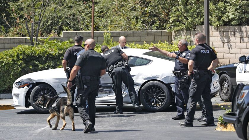 Glendale police look over a white Ford Mustang involved in an accident in La Crescenta on Tuesday, A