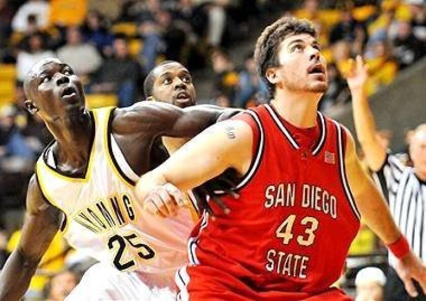 San Diego State's Ryan Amoroso (43) blocks out Wyoming's Djibril Thiam in Mountain West Conference action Wednesday at Larramie. Brandon Ewing scored 24 points and Tyson Johnson added 22 to lead Wyoming to an 83-79 win over SDSU, ending the Aztecs' five-game win streak.
