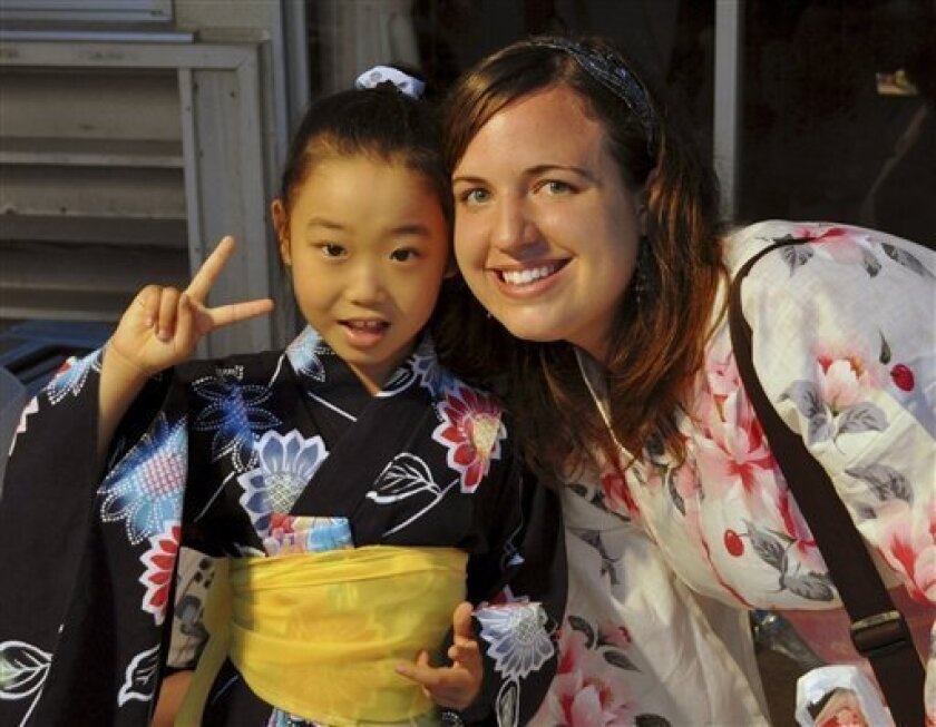 In this July 17, 2010 photo provided the Anderson family, Taylor Anderson, right, poses with one of her students in Ishinomaki, Japan, where she taught English. Anderson's family said in a statement that the U.S. Embassy in Japan on Monday, March 21, 2011 informed them by telephone of the discovery of their 24-year-old daughter's body. (AP Photo/Anderson Family) NO SALES